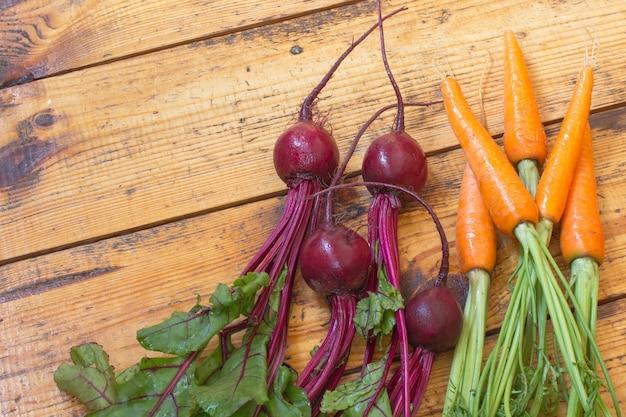 Морковь и свекла с стеблями и листьями.