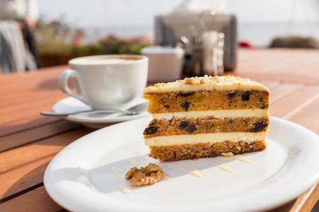 Морковно-тыквенный торт с кофейным кремом в разрезе на тарелке. вкусный нарезанный морковный пирог.