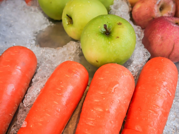Carrots, apples, green apples on fruit ice that are sold in the market