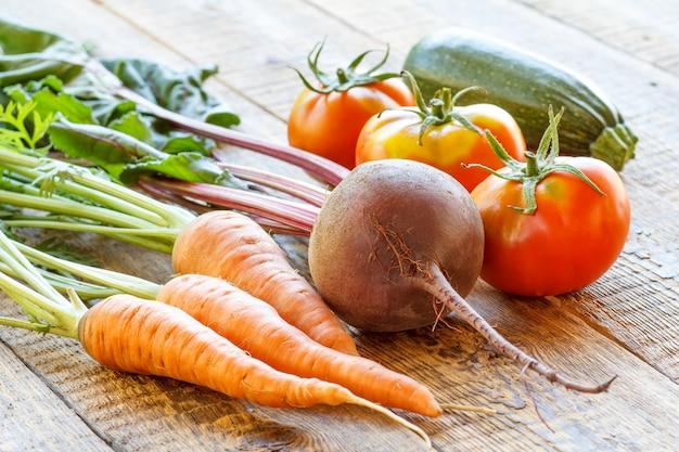 Морковь, свекла, помидоры и кабачки, только что собранные в саду на деревянных досках