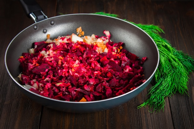 Carrots, beets and onions in a frying pan, around dill, on a brown wooden background.