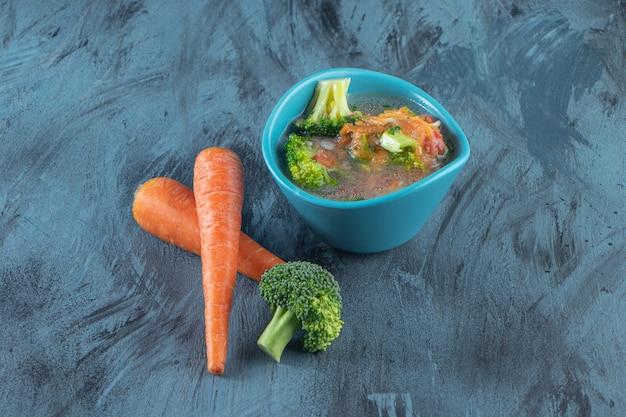Carote, broccoli e ciotola di zuppa di pollo, sulla superficie blu.