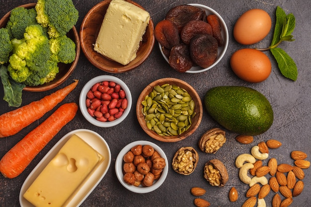 Carrots, nuts, broccoli, butter, cheese, avocado, apricots, seeds, eggs. dark background, copy space