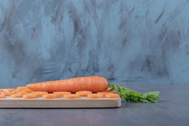 Морковь на разделочной доске, на мраморном фоне.