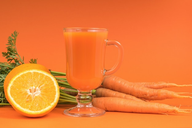 Carrots, oranges and a glass glass with a smoothie on an orange background.