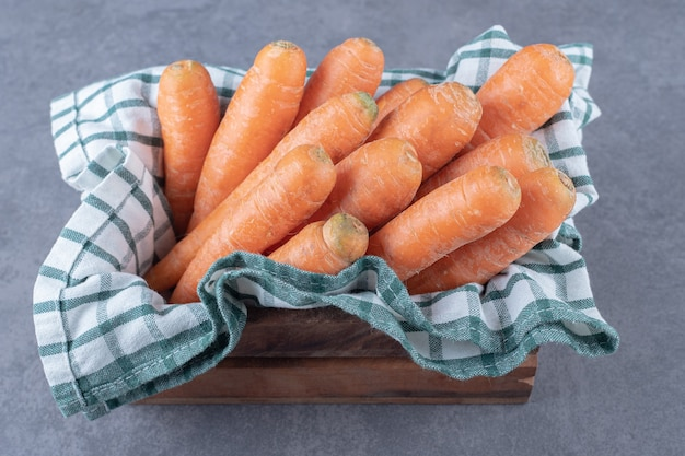 Carrots on a towel in the box , on the marble surface.