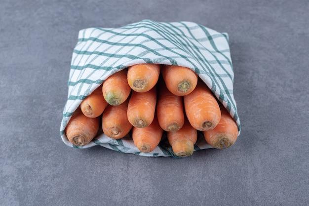Морковь, завернутая в полотенце, на мраморной поверхности.