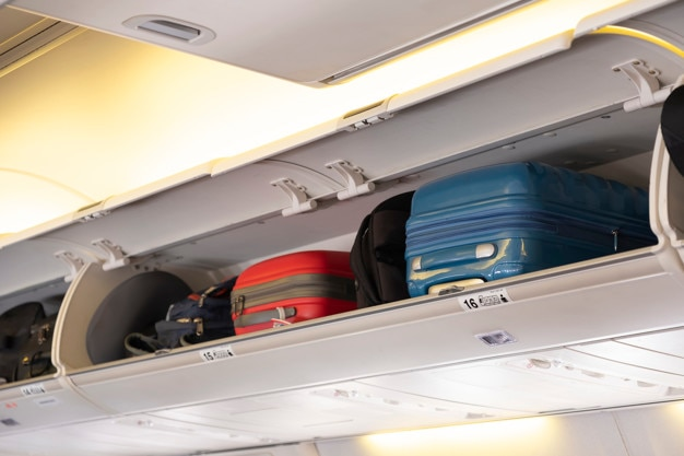 Carry-on luggage on the top shelf in airplane