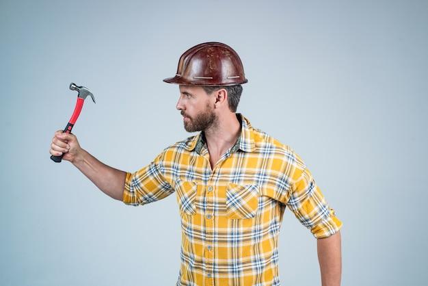 수리를 수행합니다. 망치로 남자 건축가입니다. 남자는 작업자 유니폼을 입는다. 헬멧에 잘생긴 빌더입니다. 성숙한 남자는 체크 무늬 셔츠를 입는다. 전문 생성자 또는 정비공. 빌더 엔지니어.