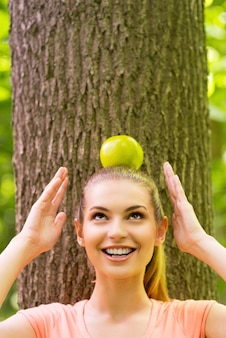 머리에 사과를 들고. 장난기 많은 젊은 여성이 사과를 머리에 이고 공원에 있는 나무에 기대어 미소를 지으며 올려다본다