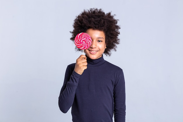 Carrying colorful candy. beaming curly young guy closing his face with sweet red candy while posing for cameramen