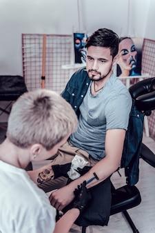 使い捨てかみそりを運ぶ。マスターがより簡単でより良い仕事のために彼の手を剃っている間、椅子に座っている穏やかなクライアント