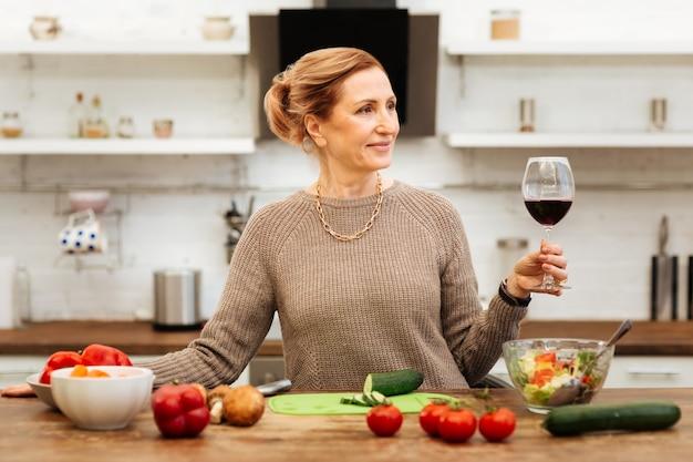 キャリンググラス。キッチンで時間を過ごし、夕食の準備をしながらワインを飲む楽しい美しい女性