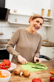 金属ナイフを運ぶ。彼女の台所で料理をしている間非常に幸せで前向きである陽気な格好良い女性