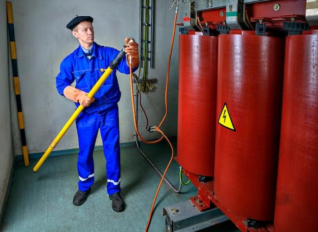 Выполняя техническое обслуживание трансформатора на токопроводящих шинах с помощью hot stick, инженер-электрик в целях безопасности накладывает временное заземление.