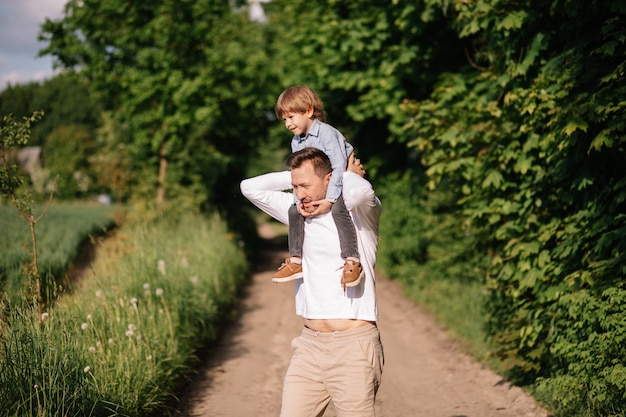 Carrying on shoulders, dad along road among forest and field, the concept of modern fatherhood