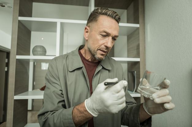 특수 브러시를 들고. 흰색 고무 장갑을 끼고 법의학 검사를 위해 립스틱 자국을 할당하는 오래된 형사