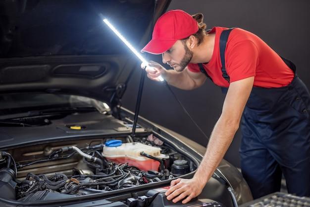 車の解剖学。内部構造を調べる車のボンネットの下に特別なランプを備えたオーバーオールの気配りのある真面目な若い男