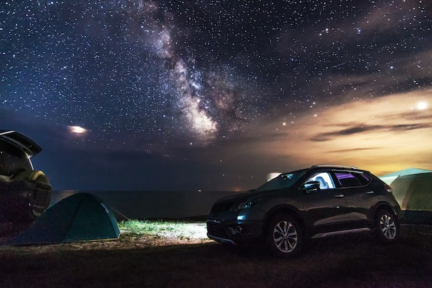 Машины и туристические палатки на пляже ночью