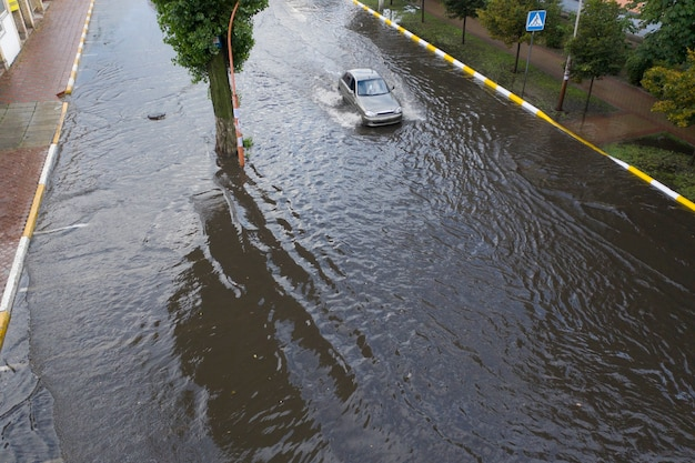Cars are moving in a heavily flooded street after an abnormal downpour.