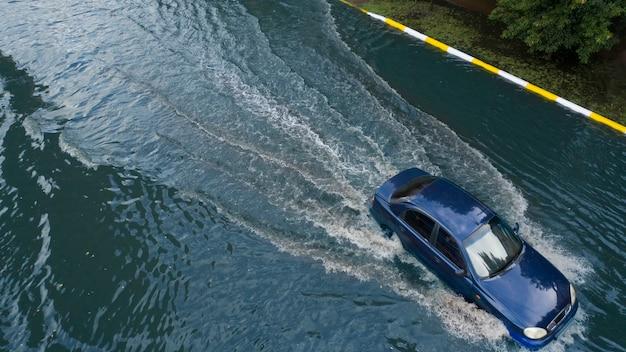 이상하게 내린 폭우로 침수된 거리에서 자동차들이 움직이고 있습니다.