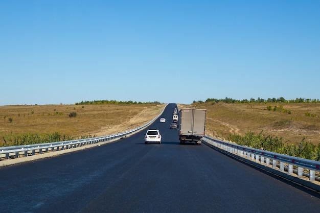 車はマーキングなしで新しいアスファルト道路を走行しています