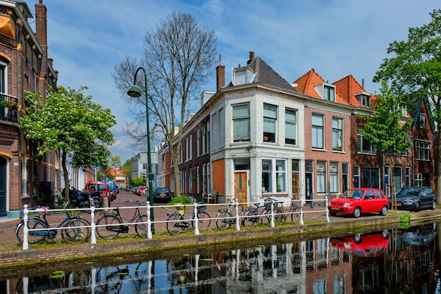 Cars on canal embankment in street of delft delft netherlands