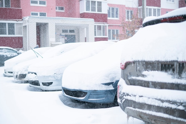 Cars covered under snow during winter, stormy weather outside