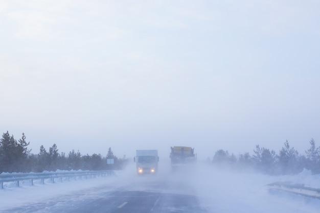 자동차는 가시성, 날씨 및 눈보라가 심한 겨울 도로를 주행합니다.