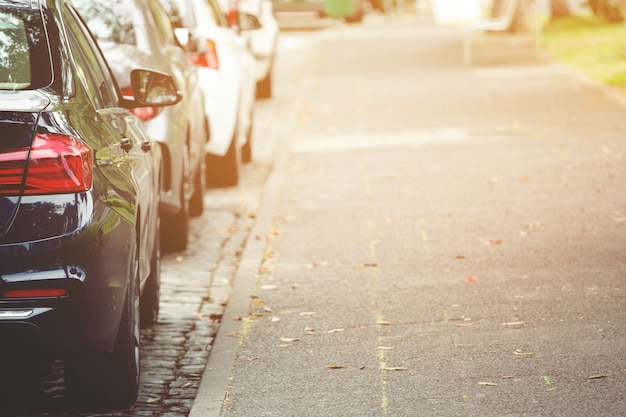 Автомобили на стоянке на открытом воздухе в ряд на обочине дороги