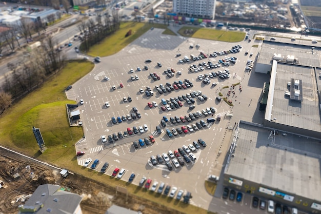 엔터테인먼트 센터 근처 주차장의 자동차-공중보기, 틸트 시프트 효과. 화창한 날에 대형 주차장에 다양한 색상의 자동차가 많이 있습니다.