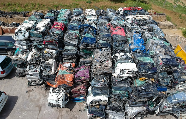 Cars in junkyard, pressed and packed for recycling.