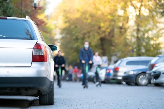 Машины припаркованы в ряд на стороне городской улицы в яркий осенний день с размытыми людьми, идущими по пешеходной зоне. Premium Фотографии