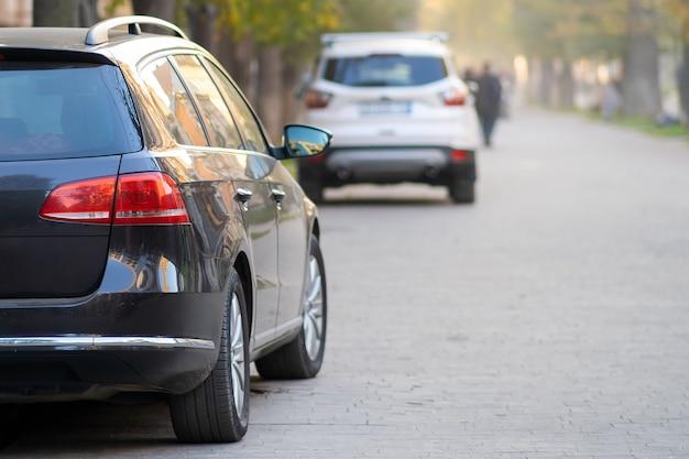 밝은 가을 날, 보행자 구역을 걷고 있는 흐릿한 사람들과 함께 도시 거리에 연속으로 주차된 자동차.