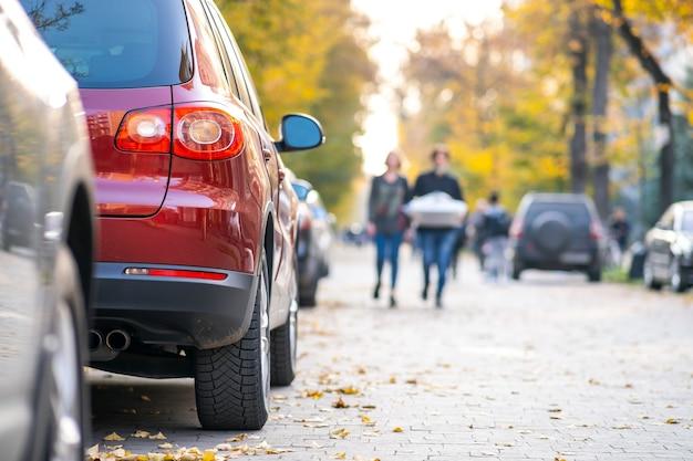 Машины припаркованы в ряд на стороне городской улицы в яркий осенний день с размытыми людьми, идущими по пешеходной зоне.