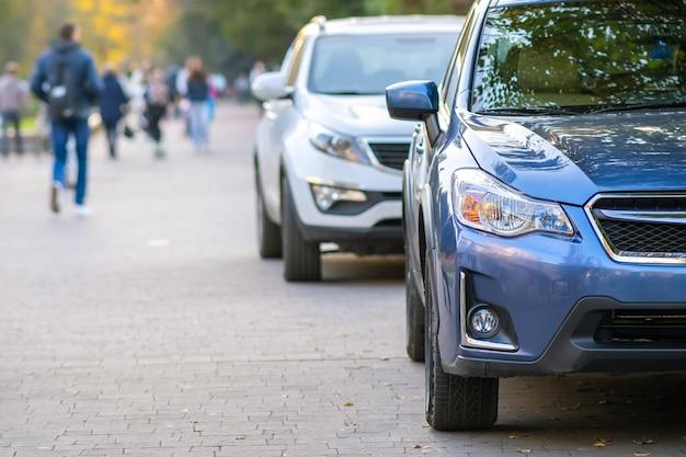 Машины припаркованы в ряд на городской улице в яркий осенний день.