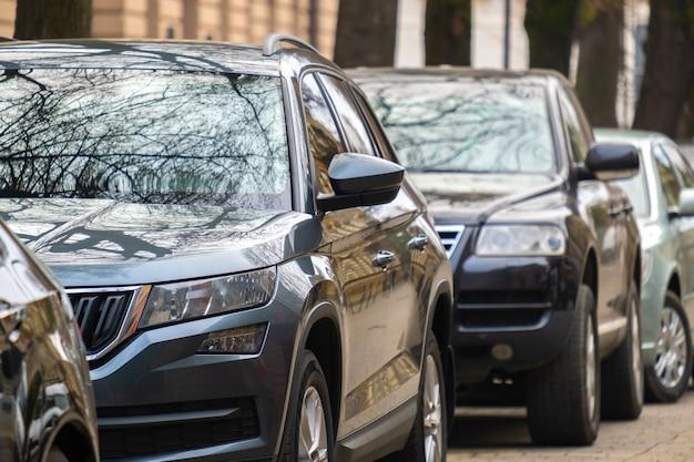 Машины припаркованы в ряд на обочине городской улицы.