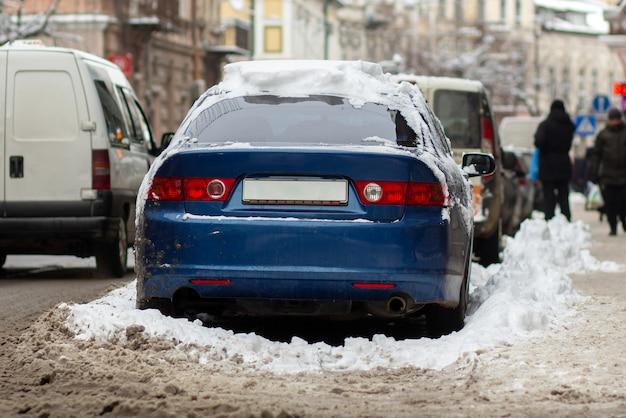 겨울에 더러운 눈으로 덮여 도시 거리의 측면에 주차 된 자동차.