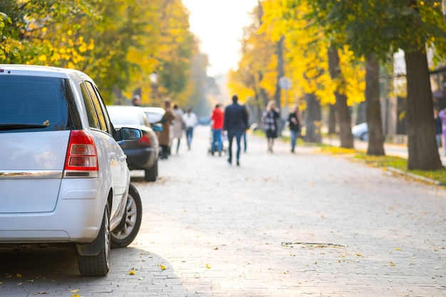Cars parked in a row on a city street side on bright autumn day with blurred people walking on pedestrian zone.