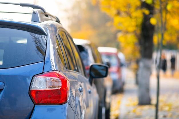 Cars parked in a row on a city street side on bright autumn day.