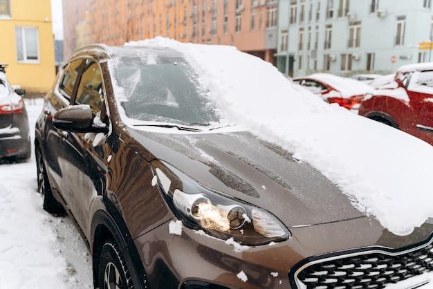 降雪後の雪の中の車。雪の降る冬、たくさんの雪。車の屋根、窓、ボンネットには雪が降っています。雪に覆われた駐車場の車。寒い雪の降る冬の天気
