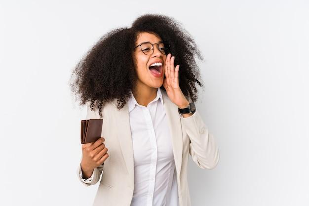 クレジットカーを保持している若いアフロビジネス女性が分離されましたクレジットcarshoutingを保持し、開いた口の近くに手のひらを保持している若いアフロビジネス女性。