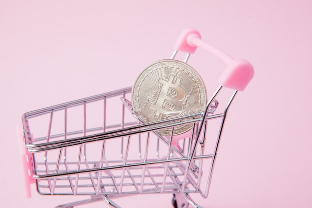 A cart from a supermarket, bitcoin on pink