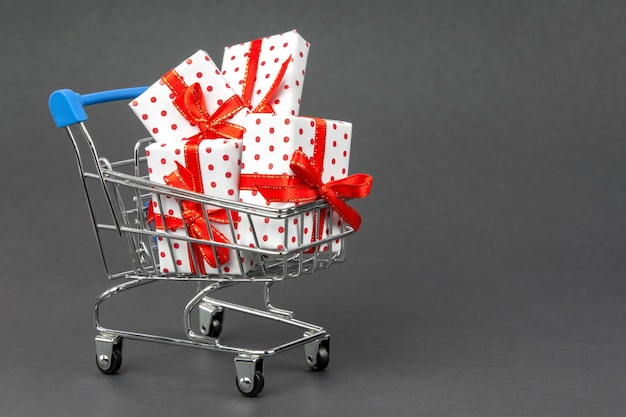 Cart full of gifts on a dark gray background with copy space. black friday and holidays concept.