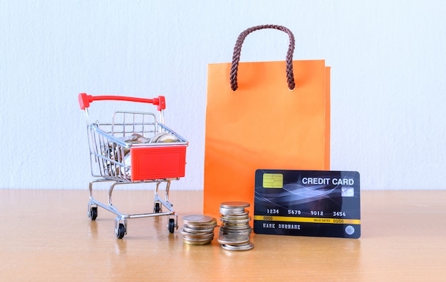 Cart supermarket and orange paper bag on wood table. shopping concept