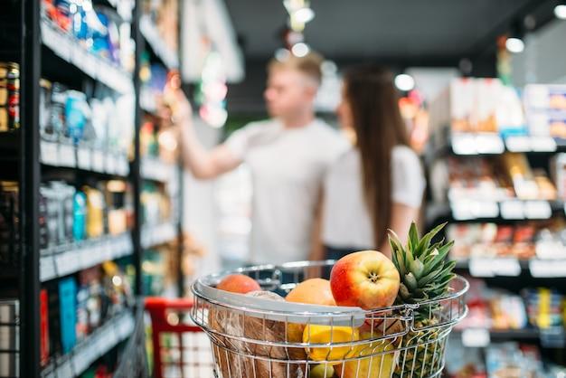 食料品店で新鮮な果物が付いているカート、カップルは背景にpruductsを見てください。スーパーマーケットの顧客またはバイヤー
