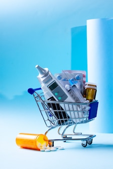 Cart with pills and thermometre over blue background