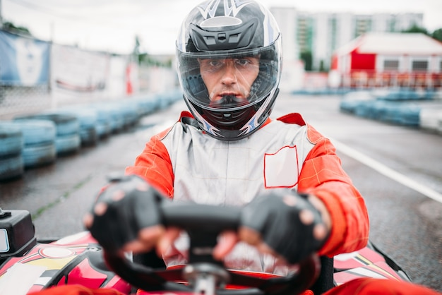 Carting race, go kart driver in helmet on karting speed track, front view.