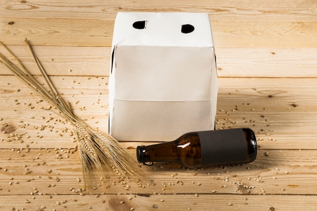 Carton box; beer bottle and ears of wheat on wooden surface