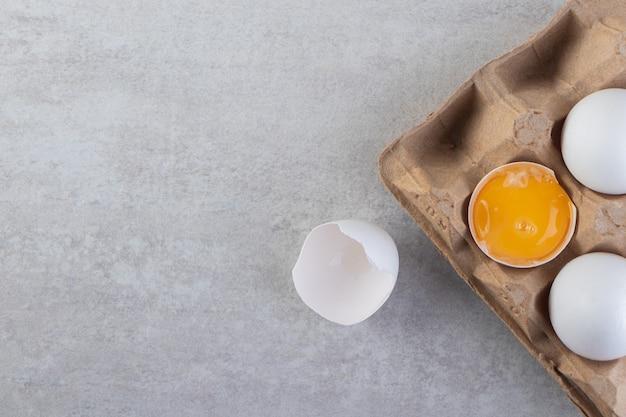 石のテーブルに白い生卵のカートンボックス。
